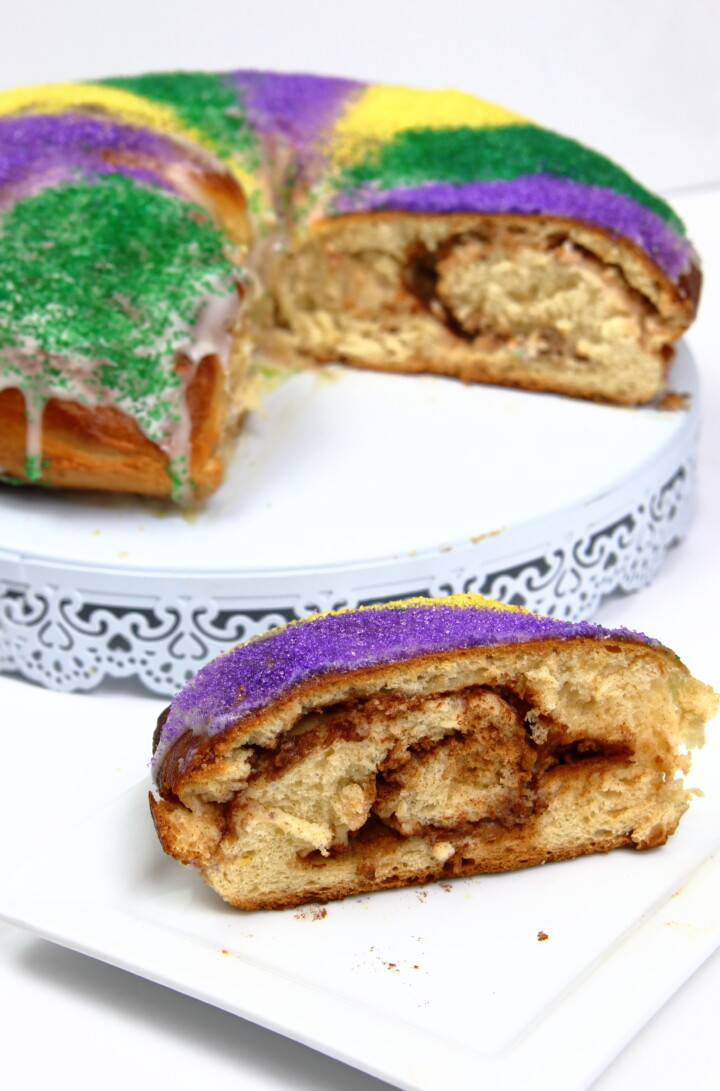 a slice of Mardi Gras King Cake with the rest of the king cake behind it
