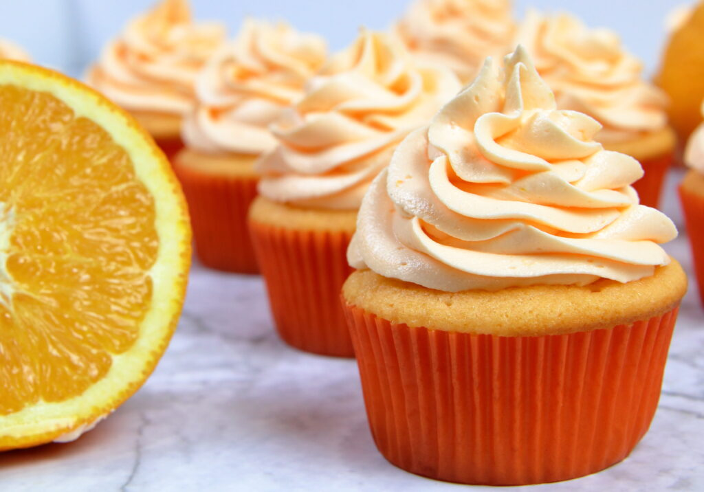 Orange Creamsicle Cupcakes next to a fresh orange cut in half