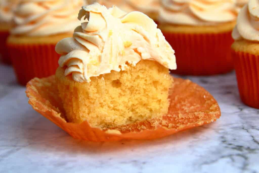 Orange Creamsicle Cupcake with a bite taken out to reveal the center