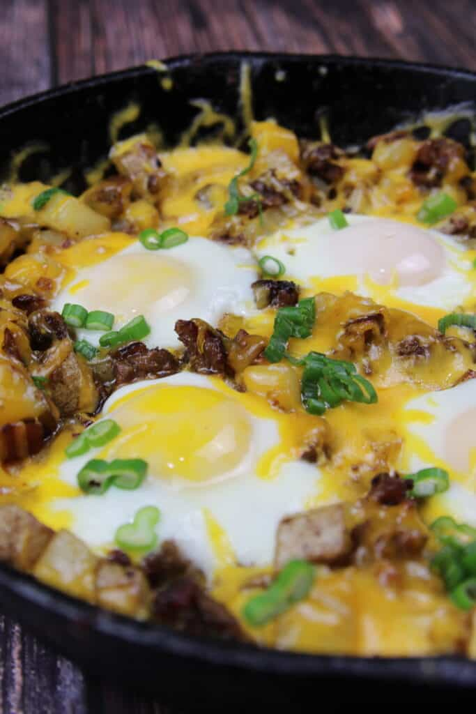 Breakfast Hash with melted cheese, over easy eggs, and potatoes in a skillet