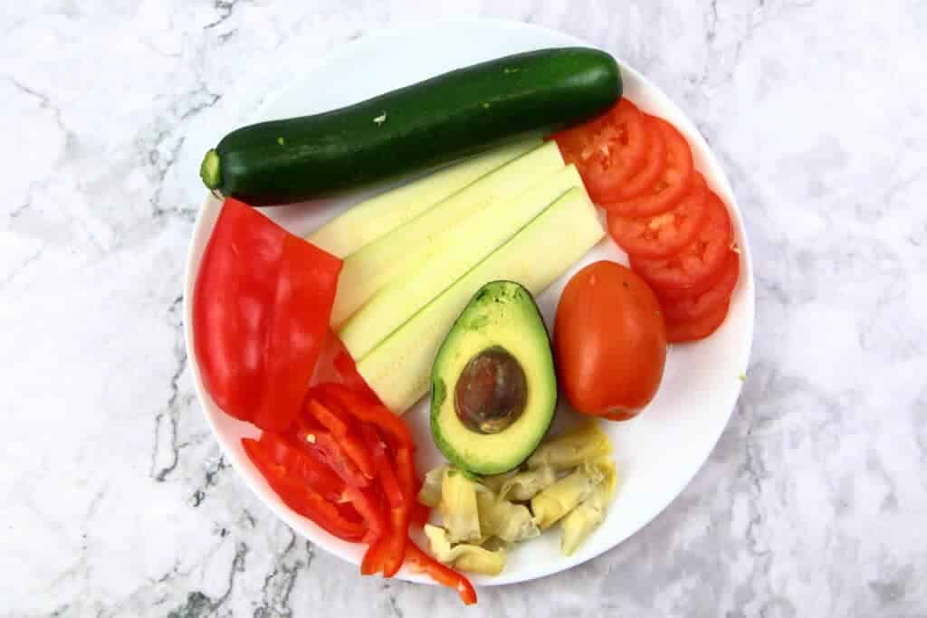 raw vegetables on a plate. Zucchini, avocado, tomatoes, red belle pepper, and artichoke.