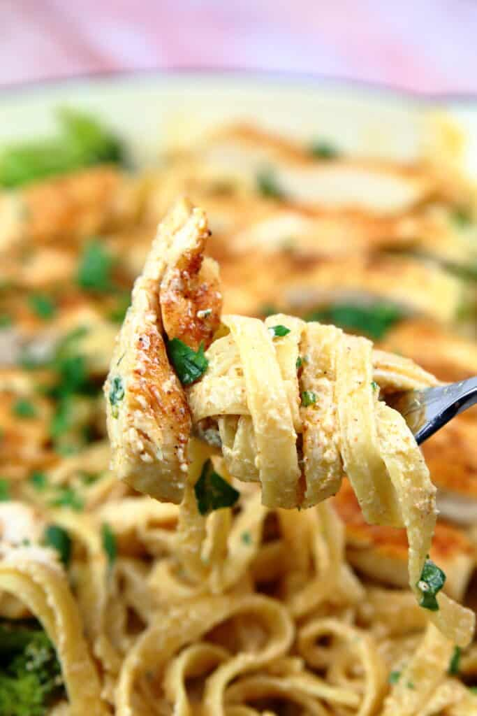 Cajun chicken pasta twirled up on a fork.