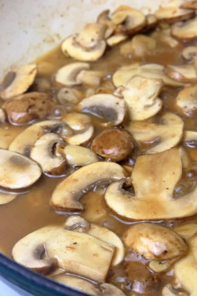 Sliced mushrooms simmering in white wine.