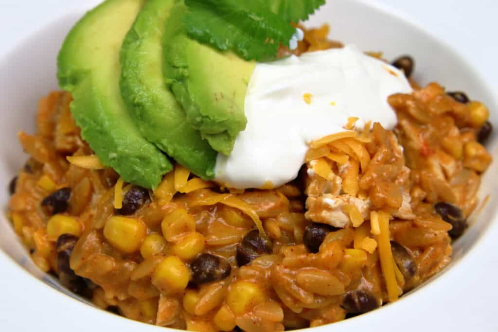 Cheesy Chicken Enchilada Bowl with sliced avocados and sour cream on top
