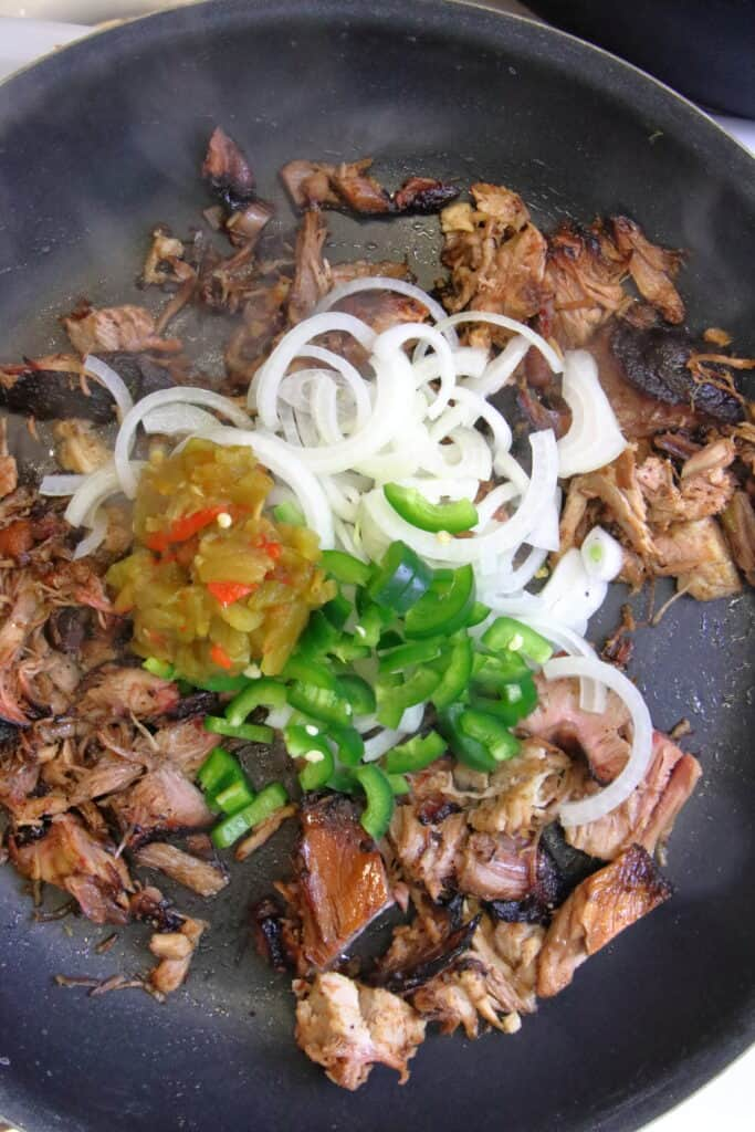 Pulled pork, peppers, onions, and green chile in a pan.