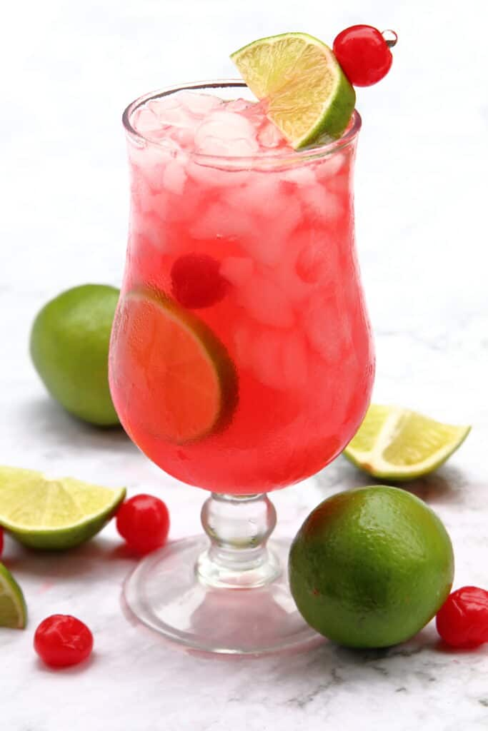 Cherry limeade with fresh cherries and limes around the bottom of the glass.