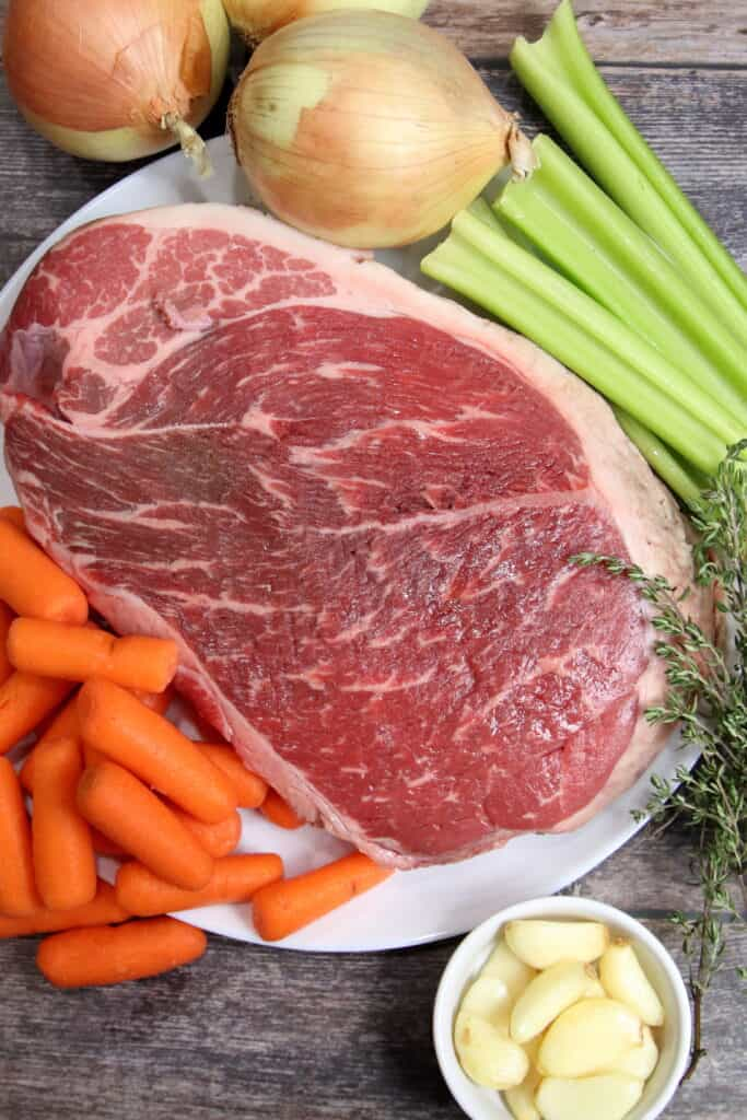 photo of raw chuck roast surrounded by uncooked onions, garlic, thyme, carrots, and celery.
