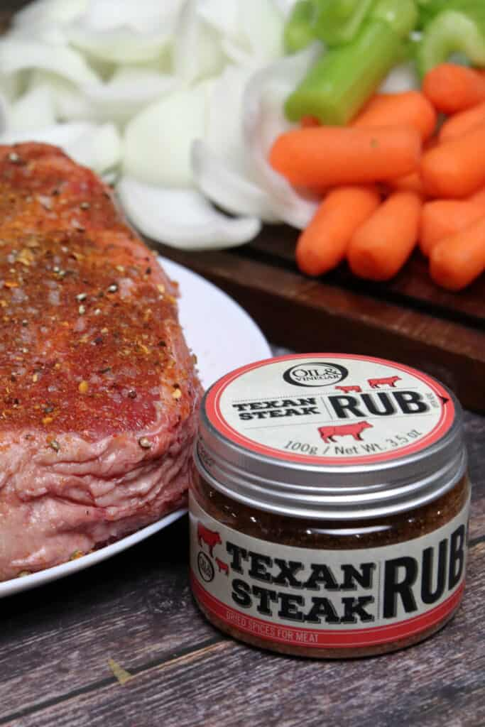 Seasoned chuck roast with veggie in the background next to a container of texan steak rub.