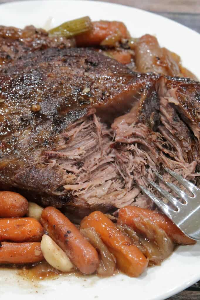 plate of chuck roast on cooked veggies with a fork tearing apart the tender meat