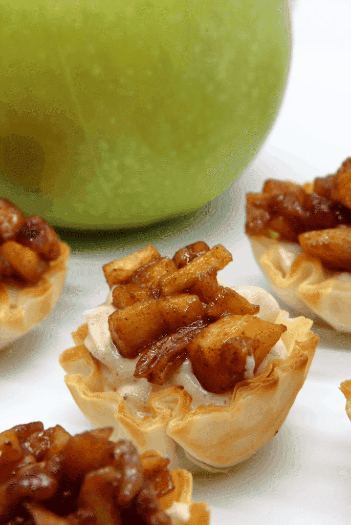 Apple cheesecake bites in front of a green apple