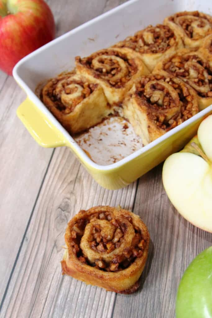 Pan of apple pie cinnamon rolls with one removed and placed on a table.