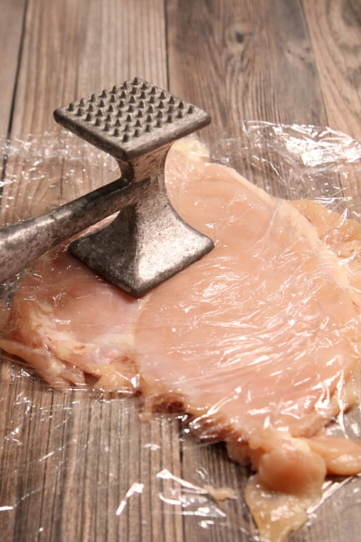 Chicken Breast between 2 pieces of plastic wrap being hammered with a meat tenderizer