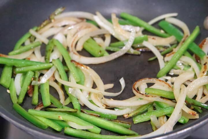 green peppers and white onions sauteed in a pan