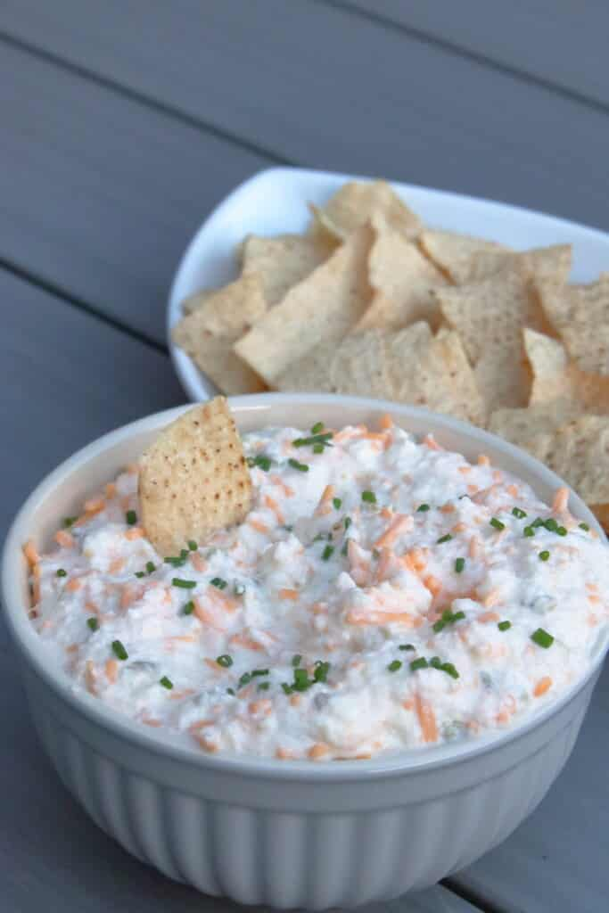 Bowl of mixed onion dip with a tortilla chip sticking in the dip.
