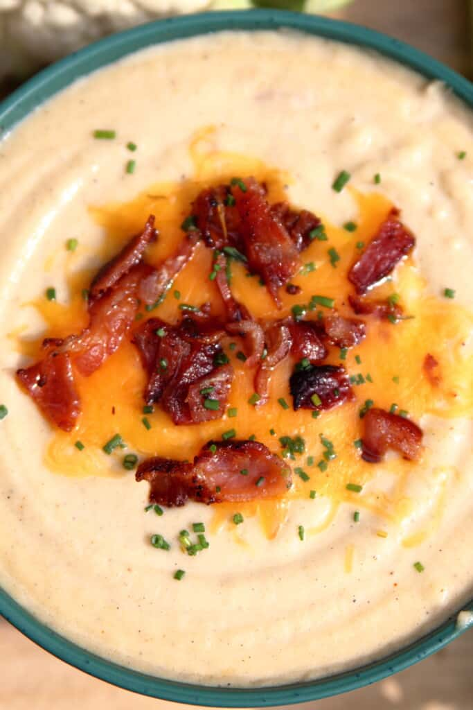 Close up of a bowl of loaded cauliflower soup with bacon, cheese, and chives