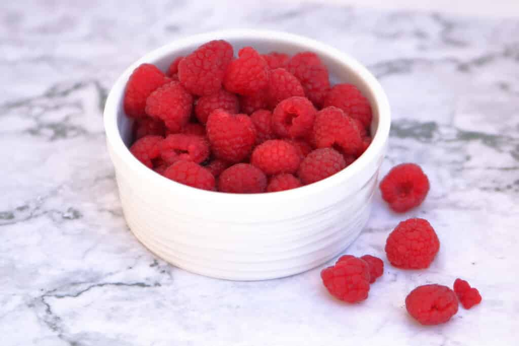 fresh raspberries in a white bowl on a white and grey marble table