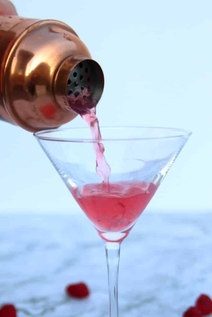 Pouring the martini into a glass.