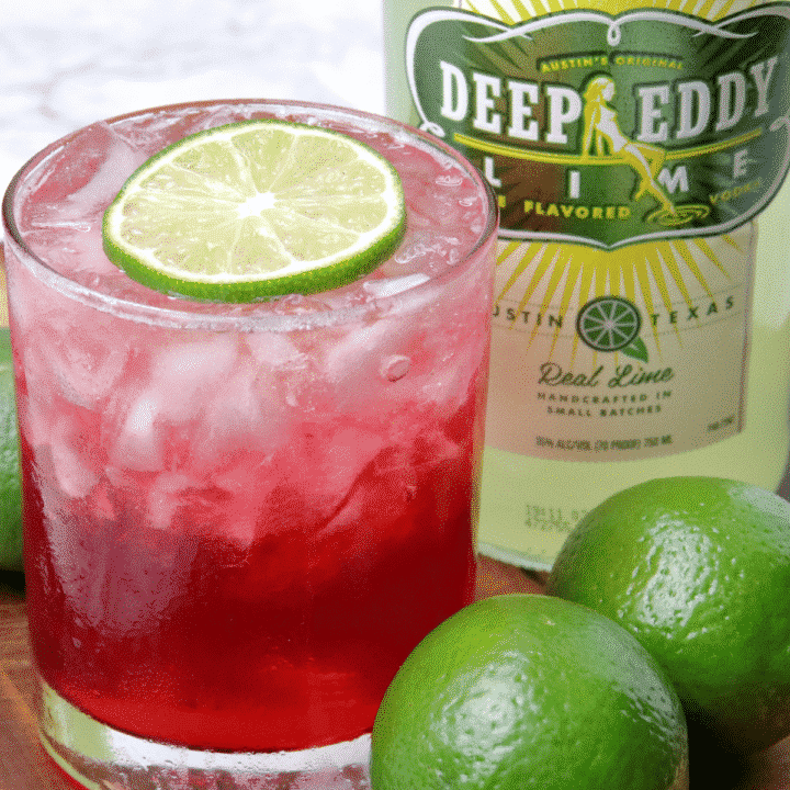 vodka cranberry cocktail with fresh limes and deep eddy vodka bottle