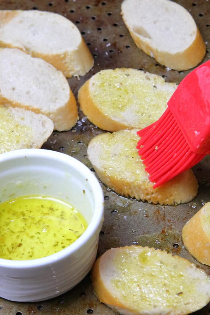Brushing melted butter on the baguette slices prior to toasting