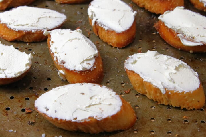Crostini on a baking pan with goat cheese spread on top