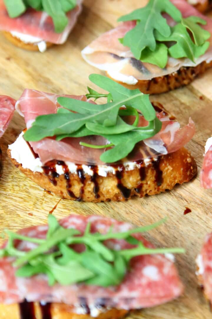 Goat cheese crostini on a wooden platter