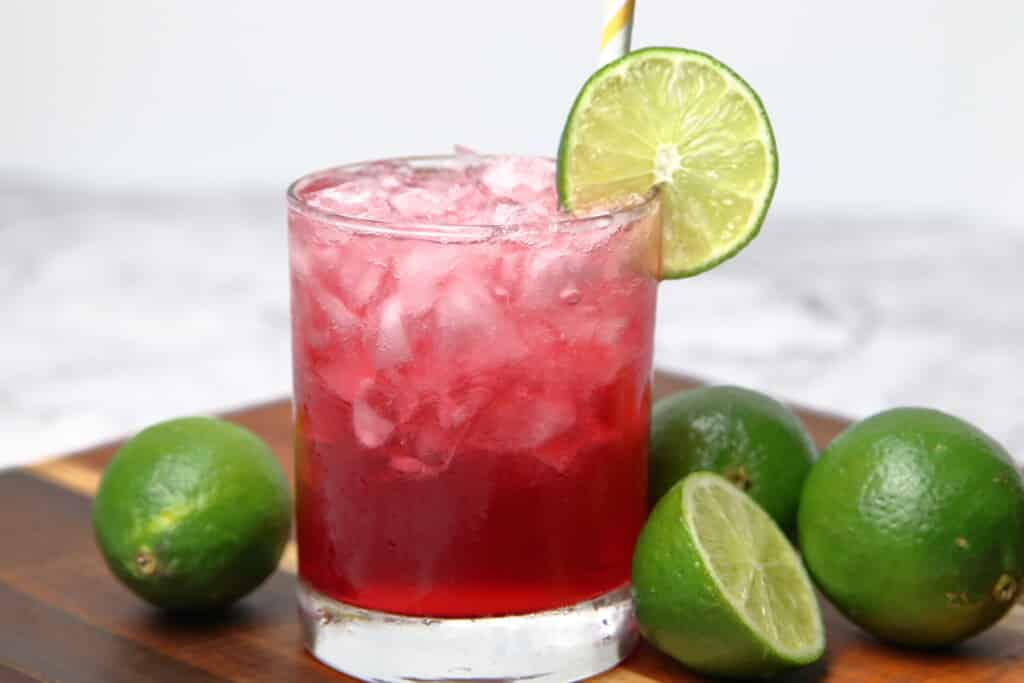 lime vodka and cranberry sparkler cocktail with a wheel of lime next to several fresh limes