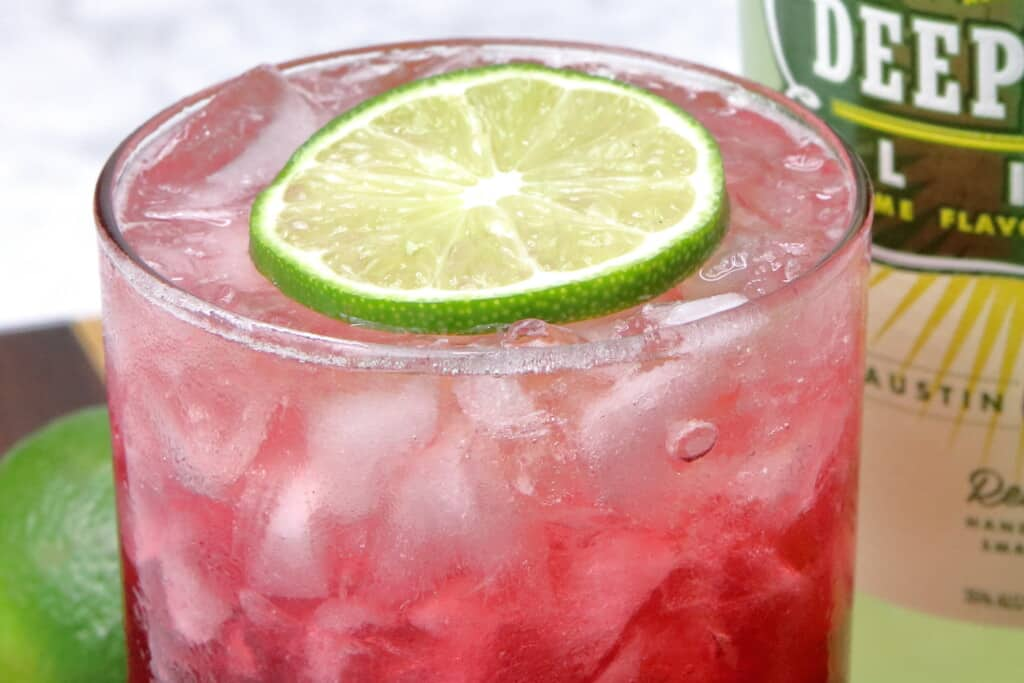 close up of the vodka cranberry with a slice of lime floating on top