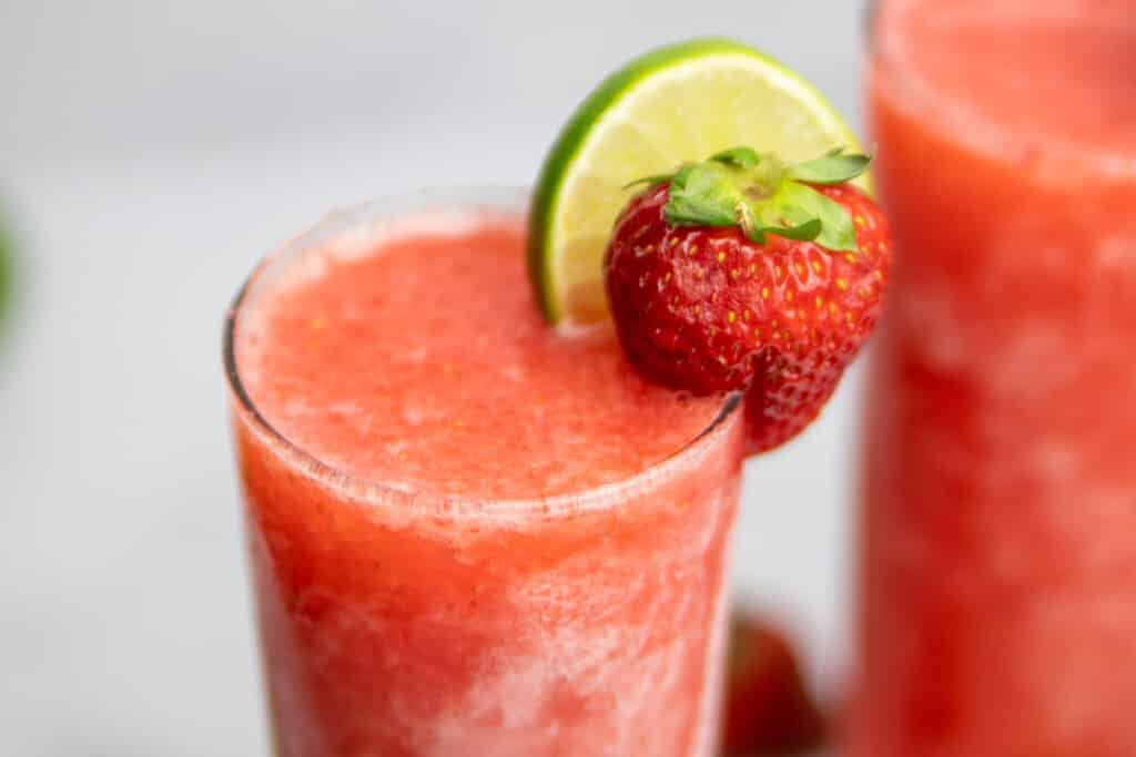 close up of the Frozen Strawberry Limeade Vodka with fresh lime and strawberry for garnish