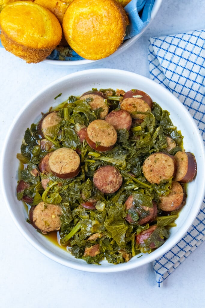 bowl of mustard greens with a bowl of cornbread on the side.