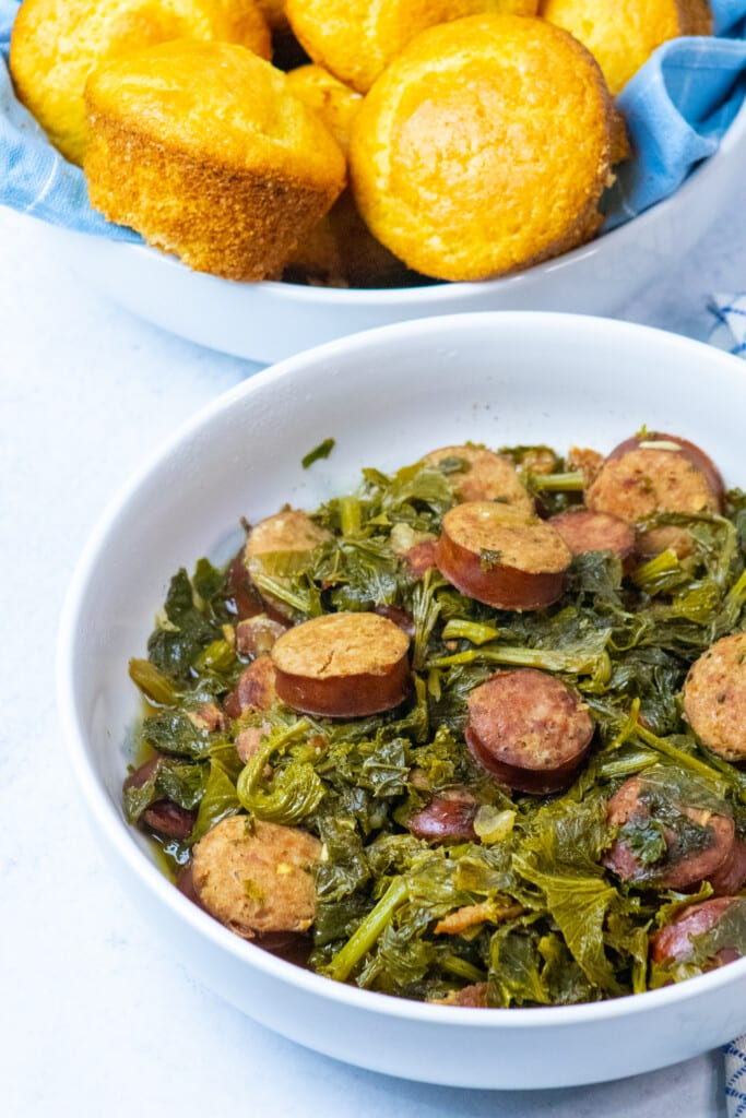 bowl of mustard greens and sausage next to a bowl of cornbread.